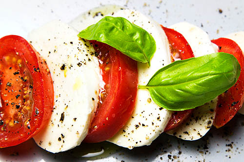Tomato and mozzarella salad with fresh basil leaves black pepper and olive oil